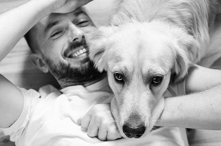 grayscale photo of man with dog