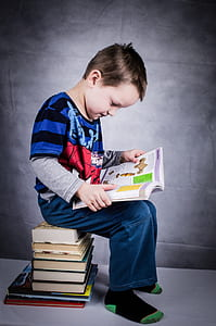 boy reading book sitting on stack of books