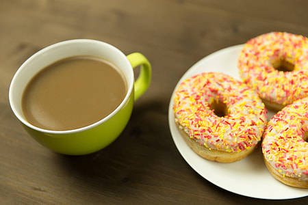 Coffee cup and donuts on desk