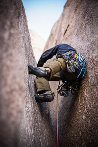 man doing rock climbing in between of gray rock formation