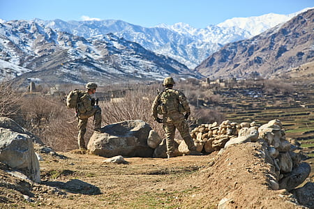 two soldiers on rocky ground during daytime