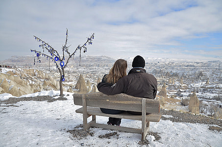 photo of couple sitting on brown bench while staring at the horizon