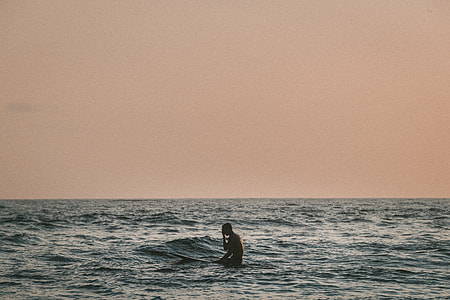 photography of surfer in the middle of the sea