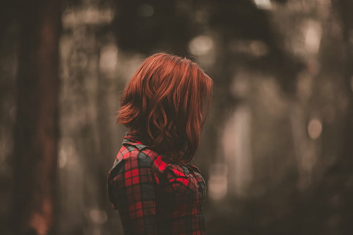 woman with short red hair wearing red and black plaid shirt