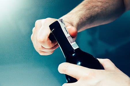 person opening black glass bottle