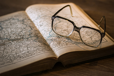 Map in open book and reading glasses