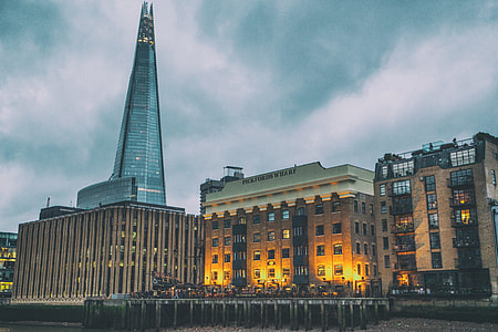 Wide angle shot taken from the River Thames in London. On the side of the river are Pickfords Wharf and The Shard skyscraper