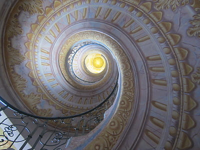 low angle of white and yellow floral spiral staircase ceiling