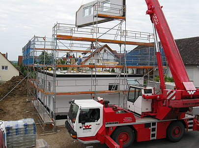 red and white crane truck lifting white building frame