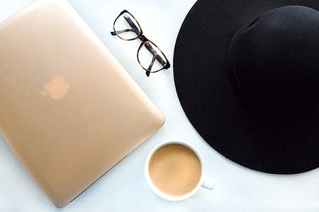 macbook beside eyeglass and mug