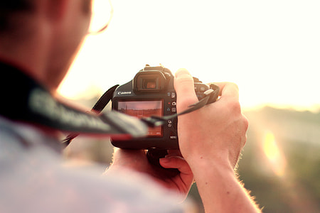 man holding black DSLR taking picture of scenery
