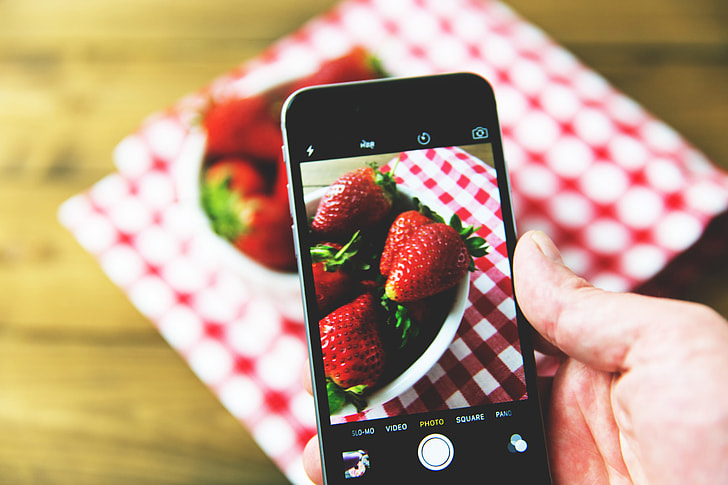 Man taking a photo of fresh strawberry fruit on his mobile iPhone smartphone