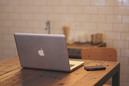 silver MacBook on brown table