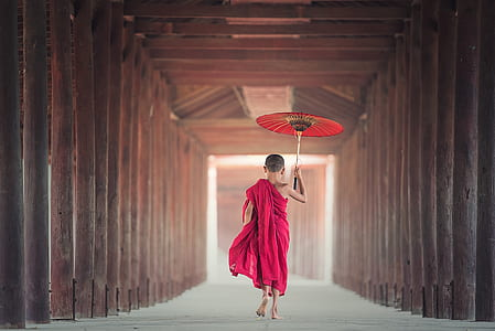 person in pink dress holding red oil paper umbrella