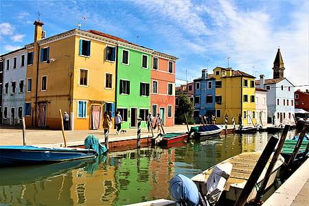 assorted colored concrete 3-storey houses under calm blue sky