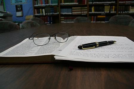 black pen beside eyeglasses on top of book