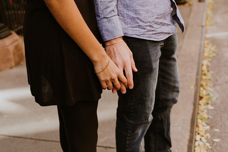 two person holding hands near road