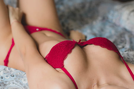 woman wearing red lace push-up bra panty while lying on bed