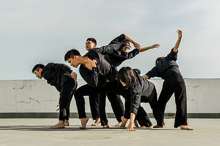 Six People in Black Matching Clothes Dancing at Daytime