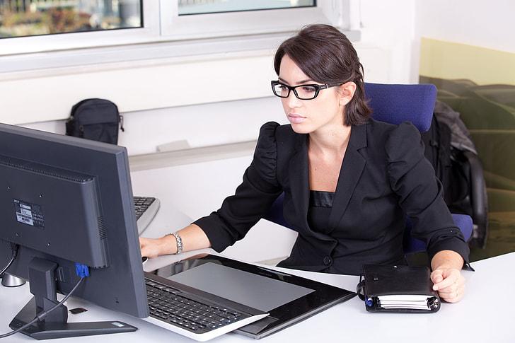 woman using computer wearing black blazer