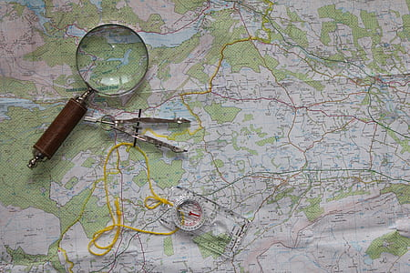 photo of magnifying glass and ruler on map