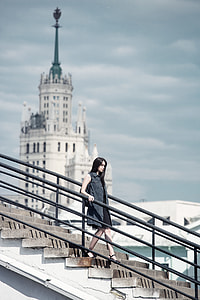 depth of field photography of woman walking down the stairs