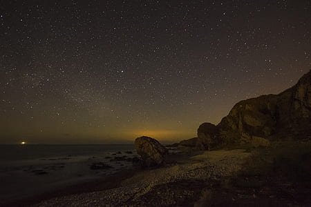 time-lapse photography of brown rock formation under stars
