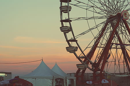 red and white ferris wheel near two white canopy tent during sunset