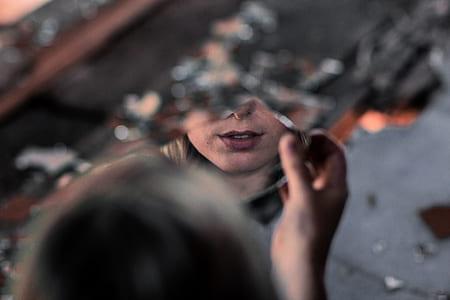 woman holding broken piece of glass