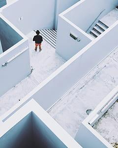 person wearing black top beside white concrete wall