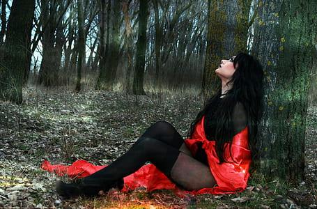 woman wearing red and black mesh bodysuit sitting beside tree