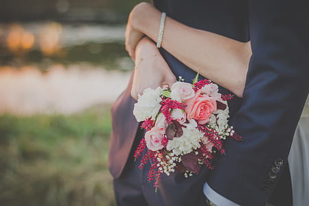 woman hugging a man while holding flower bouquet