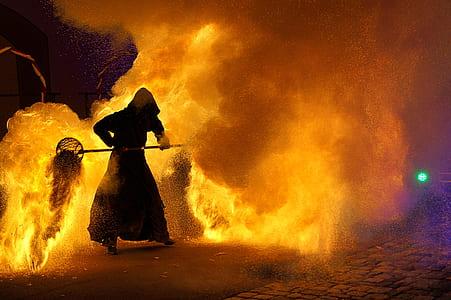 man holding tool near fire