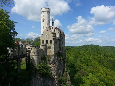 photography of gray stone castle on peak of mountain