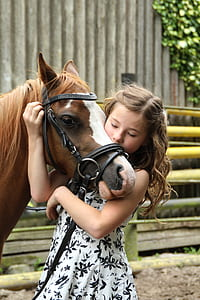 girl wearing white and black floral dress hugging brown horse head during daytime