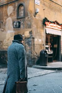 person wearing gray coat walking in village