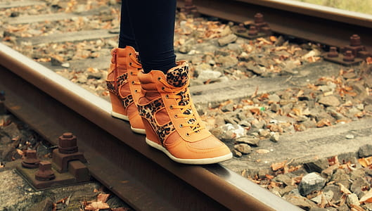 person wearing brown leather wedge sneakers on train rail