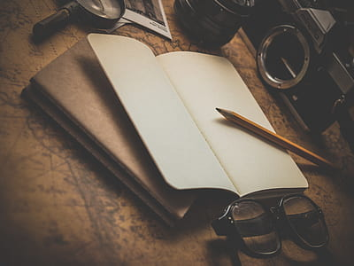 pencil, black framed eyeglasses, book, camera, and magnifying glass on brown surface