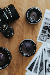 Old Zenit camera and a Canon camera with black-and-white photos on a wooden table