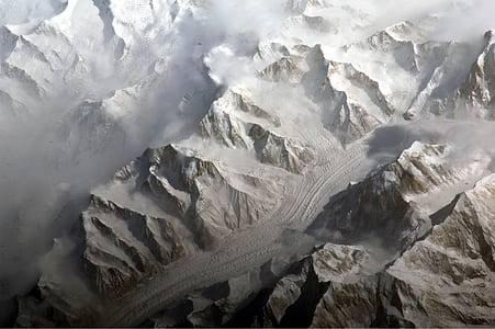 aerial photography of road in between snow capped mountains