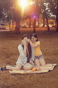 Two Women Sitting on Brown Picnic Mat during Sunset