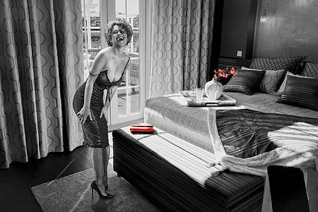 grayscale photo of woman standing near mattress