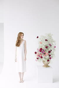 Woman in White Spaghetti Strap Midi Dress Standing Beside Table With Flowers