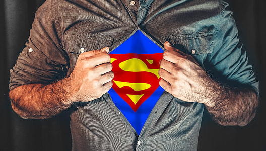 man opening his shirt showing a superman symbol on his inner shirt