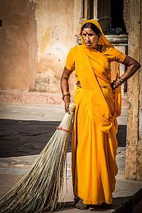 woman in yellow sari dress holding broomstick