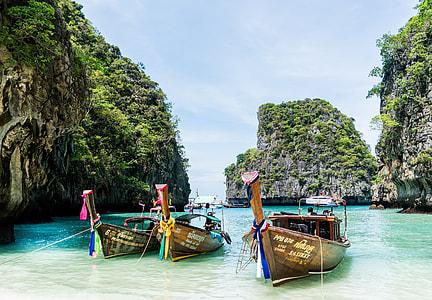 three brown wooden boats on seashore