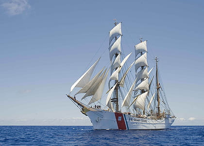 white and red galleon ship under blue sky