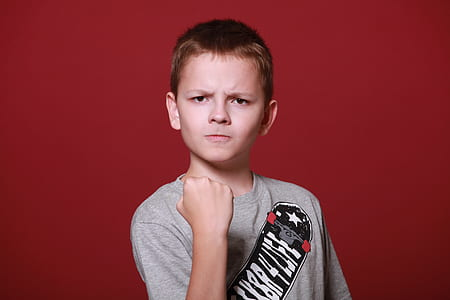 boy in red shirt showing fist