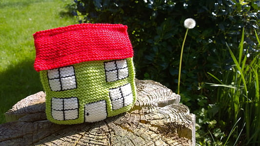 green and red knit miniature house on brown wood slab near green plants at daytime