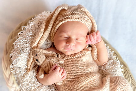 baby wearing brown knitted shirt
